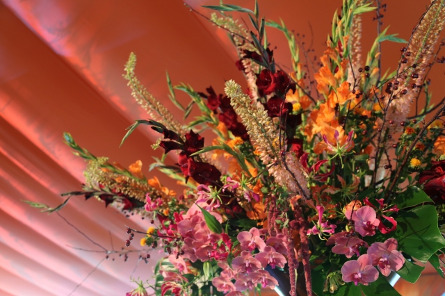 A stage piece blending gloriosa lilies, pink phales, eremurus, gladiolus, crab apple and amaranthus